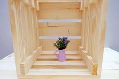 Caja de madera con la pequeña flor púrpura en pote Imagen de archivo libre de regalías