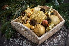 Caja de madera con las decoraciones de oro de la Navidad Fotos de archivo libres de regalías