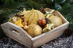 Caja de madera con las decoraciones de oro de la Navidad en la tabla Imagenes de archivo
