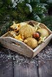 Caja de madera con las decoraciones de oro de la Navidad en la tabla, vertical Imagenes de archivo