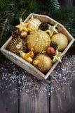 Caja de madera con las decoraciones de oro de la Navidad en la tabla, vertical Foto de archivo libre de regalías