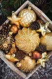 Caja de madera con las decoraciones de oro de la Navidad, vertical, visión superior Fotografía de archivo