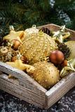 caja de madera con las decoraciones de oro de la Navidad, verticales Imagen de archivo