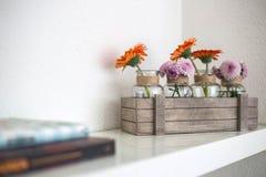 Caja de madera con las flores anaranjadas y rosadas en el estante blanco, fondo blanco, dise?o moderno foto de archivo