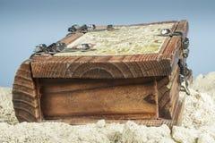 Caja de madera con un mapa en la arena de la playa Fotos de archivo libres de regalías