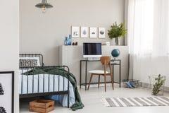 Caja de madera debajo de la sola cama del metal con las hojas azules y la manta verde en el sitio del niño de moda con espacio de fotos de archivo libres de regalías