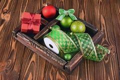 Caja de madera del vintage con las bolas del árbol de navidad, la cinta y la caja de regalo Fotografía de archivo libre de regalías