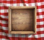 Caja de madera en la opinión superior del mantel rojo de la comida campestre fotografía de archivo