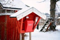 Caja de madera roja del poste del correo del viejo vintage en el pueblo del campo en invierno imagenes de archivo