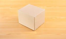 Caja de papel acanalada en la tabla de madera Imagen de archivo libre de regalías