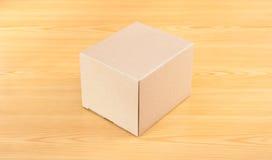 Caja de papel acanalada en la tabla de madera Imagen de archivo