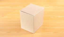 Caja de papel acanalada en la tabla de madera Fotografía de archivo
