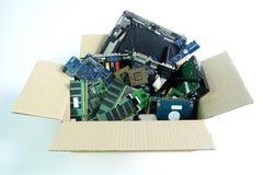 Caja de papel con la basura electrónica de la pieza del hardware aislada en blanco imagen de archivo libre de regalías