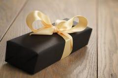Caja de papel del negro hecho a mano del regalo con el arco amarillo de la cinta en la tabla de madera foto de archivo
