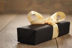 Caja de papel del negro hecho a mano del regalo con el arco amarillo de la cinta en la tabla de madera imagen de archivo