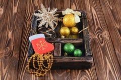 Caja de recuerdos del vintage con la bola de oro y verde de la Navidad en el fondo de madera Fotos de archivo libres de regalías