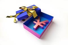 Caja de regalo abierta con una cinta de oro y el símbolo de los yenes dentro. Fotografía de archivo libre de regalías