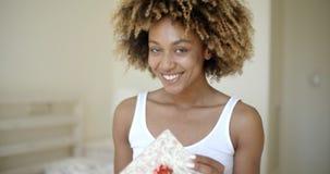 Caja de regalo abierta feliz de la mujer joven en dormitorio almacen de metraje de vídeo