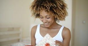 Caja de regalo abierta feliz de la mujer joven en dormitorio Imagen de archivo libre de regalías