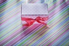Caja de regalo adornada en concepto rayado de las celebraciones del mantel Fotos de archivo