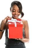 Caja de regalo afroamericana de la abertura de la mujer foto de archivo libre de regalías