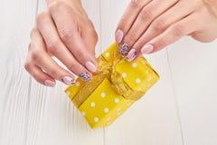 Caja de regalo amarilla en manos femeninas Foto de archivo