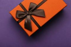 Caja de regalo anaranjada con el arco marrón en un fondo púrpura Imagen de archivo