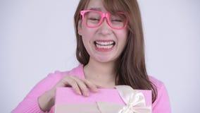Caja de regalo asiática feliz joven de la abertura de la mujer del empollón y el parecer sorprendido almacen de metraje de vídeo