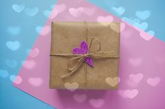 Caja de regalo atada con la cinta roja en fondo azul en colores pastel imagen de archivo