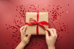 Caja de regalo atada con la cinta roja en fondo rosado en colores pastel foto de archivo