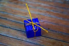 Caja de regalo azul en el fondo de madera Caja de regalo de la Navidad en el follaje que envuelve con el hilo del oro Fotos de archivo libres de regalías