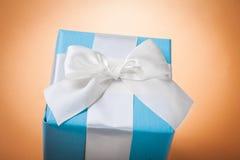 Caja de regalo azul en fondo marrón claro Fotografía de archivo libre de regalías