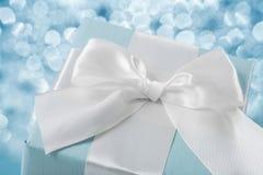Caja de regalo azul de la visión superior con el arco blanco en fondo borroso Imagen de archivo libre de regalías