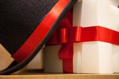 Caja de regalo blanca atada con la cinta roja elegante y el sombrero negro lanzamiento del cierre para arriba Fotografía de archivo libre de regalías
