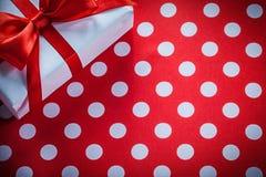 Caja de regalo blanca con la cinta atada en celebrat rojo de la tela del lunar imagen de archivo libre de regalías
