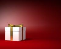Caja de regalo blanca con la cinta del oro y arco en el fondo rojo Fotos de archivo