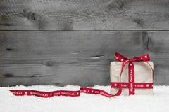 Caja de regalo blanca con la cinta larga roja y arco en backg de madera gris Fotos de archivo