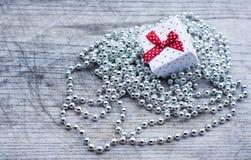 Caja de regalo blanca con los puntos rojos sobre las perlas de plata Imagen de archivo libre de regalías