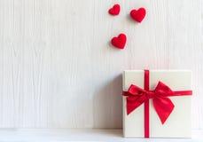 Caja de regalo blanca del día de tarjetas del día de San Valentín con un arco rojo en el fondo blanco de la pared, fotos de archivo libres de regalías