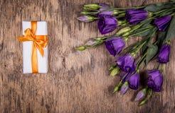 Caja de regalo blanca en un fondo arbolado y un ramo de flores púrpuras Las flores delicadas son eustoma Fotografía de archivo libre de regalías