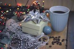 Caja de regalo blanca, taza azul, bola azul y gotas en el tablenn Imagen de archivo