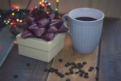 Caja de regalo blanca, taza azul, granos de café en el tablen Imagen de archivo