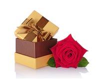 Caja de regalo brillante clásica de oro con el lazo de satén marrón y la rosa hermosa del rojo Imagen de archivo