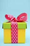 Caja de regalo brillante del color en fondo rosado y azul Imágenes de archivo libres de regalías