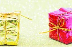 Caja de regalo brillante de la Navidad en fondo chispeante Oro amarillo y papel de envoltorio para regalos rojo Fotos de archivo libres de regalías