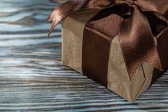 Caja de regalo de Brown con el arco atado en fondo de madera imagenes de archivo