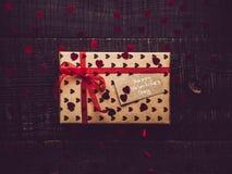 Caja de regalo colorida en un fondo superficial oscuro imagen de archivo