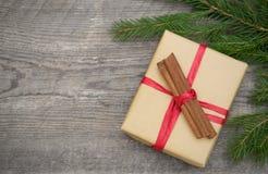 Caja de regalo con canela en fondo de madera imagenes de archivo