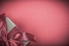 Caja de regalo con el arco atado en concepto rojo de los días de fiesta del fondo Foto de archivo libre de regalías