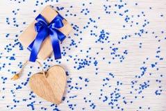 Caja de regalo con el arco azul y tarjetas del día de San Valentín en un fondo blanco con las chispas Día del `s de la tarjeta de Imagen de archivo libre de regalías